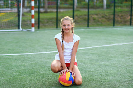 Girl with a ball in her hands on the playground