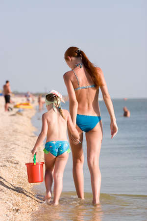 child s: Mother and daughter walk on seacoast Stock Photo