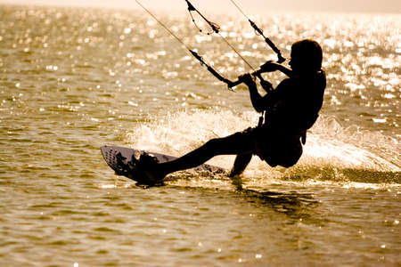 inshore: Silhouette of the man on a decline engaged Kiteboarding