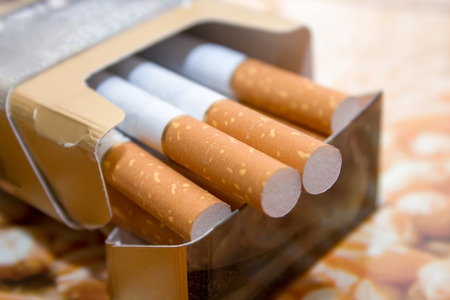 Cigarettes in a pack. Yellow filter. Harm to health. Bad habit. A pack of cigarettes on the table. open pack of cigarettes. Stock Photo