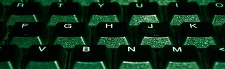 Panorama of a fragment of a computer keyboard in green backlight. programming and technology. input information