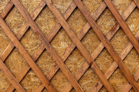 Wooden lattice with diamond shaped holes attached to a wood plate. Decorative background of boards in the form of rhombuses. Wooden decoration of geometric shapes