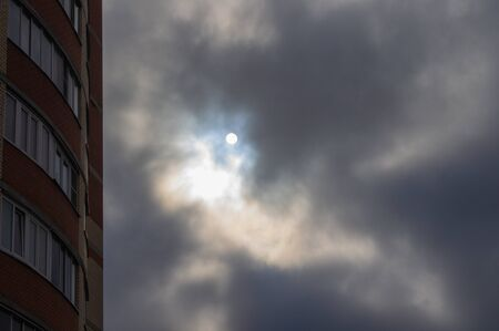 The sun breaking through the clouds in an urban area. A sharp change in weather. Clouds hanging over the house