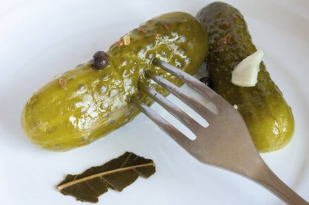Pickled cucumbers on a white plate impaled on a fork. Crispy pickled cucumbers on a white plate. Close-up of a pickled cucumber impaled on a fork Imagens