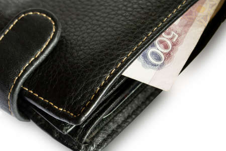 Men's leather wallet with a bill sticking out of it isolate close-up