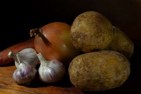 Still life vegetables low key hard light. Vegetables potatoes garlic onion close-up