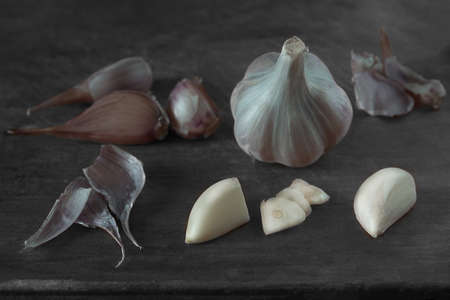 Peeled clove of garlic surrounded by unpeeled cloves of garlic lying on a wooden background