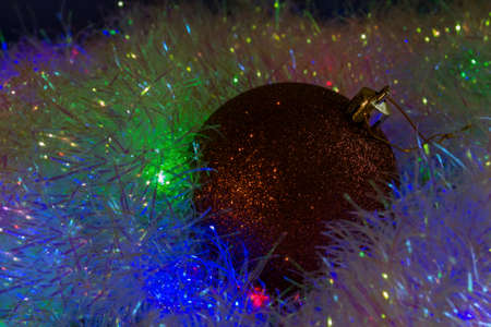 New Year's Eve background from a Christmas tree toy lying on tinsel illuminated from below with a multi-colored gerland. Christmas background in low cryptic key