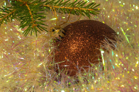 christmas background ball lying on a shiny tinsel next to a spruce branch. Christmas background decoration ball and fir sprig close up
