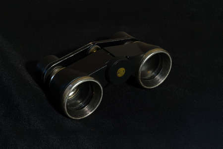 Shabby old theater binoculars lying on black cloth close-up Banco de Imagens