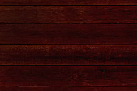 dark background from smooth mahogany boards top view. dark red wood texture evenly lit Banco de Imagens