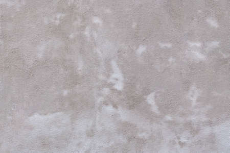 light gray concrete wall texture evenly illuminated. gray rough background with small sprinkles and light streaks
