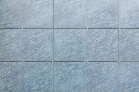 background of light blue facade tiles under soft light. facade tile texture close-up