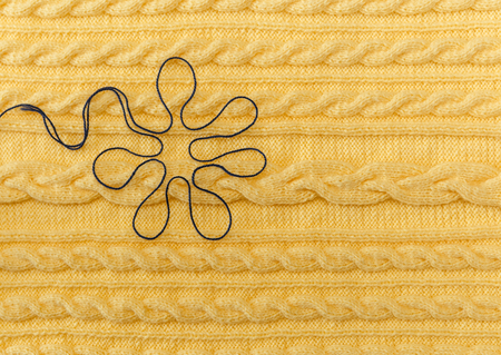 stitchcraft: Yellow Knitted Background with Pattern and Braids and Blue Floer.Hand Made;Fancywork. Stock Photo