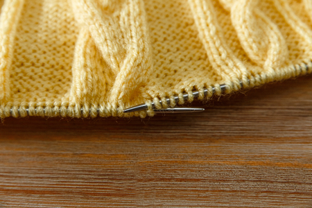 Yellow Knitted Work in Process,Grey Knitting Needles.Hand Made;Fancywork.Wooden Background