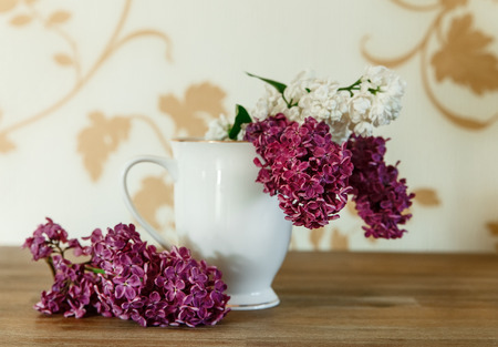Two Branch of White and Purple Lilac in the Ceramic Cup.Wooden Background,Selective Focus