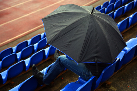 tribune: A man under an umbrella in the tribune