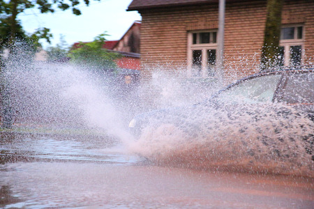 enters: The car enters into a puddle and splashing all around Stock Photo