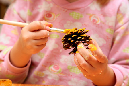 The child painting pinecone in yellow colour