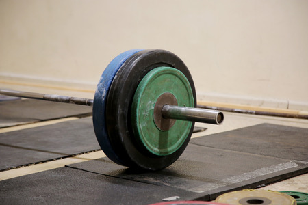 disks: Rod with different disks on the floor in the gym Stock Photo