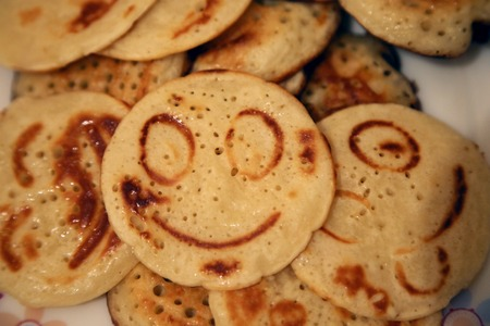 funny food: The ruddy pancakes with smiles on the plate. Funny food
