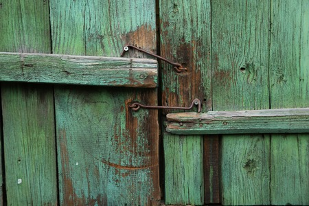 pitting: The old green shutters of window with metallic hooks. Abstract