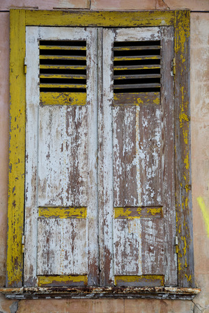 shutting: The window of old house with shutting shutters covered bt shabby paint