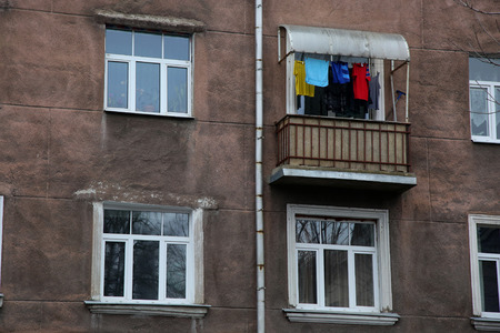 balcony window: Four window of dark house with balcony and drying clothes Stock Photo