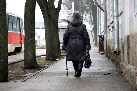 anno: Alone old woman walking on the  street with stick Stock Photo
