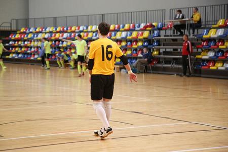 Rear view of futsal goalkeeper in yellow jersey Stock Photo