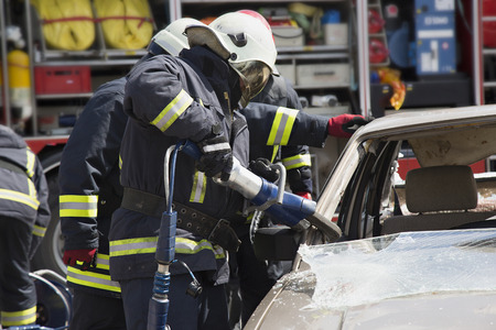 firefighters with the pneumatic shears open the car doors after a car accident Stok Fotoğraf