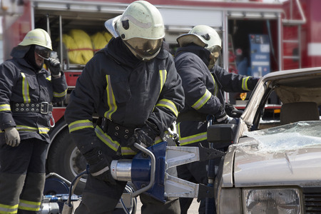 car door: firefighters with the pneumatic shears open the car doors after a car accident Stock Photo