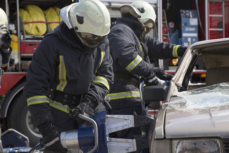 pneumatic: firefighters with the pneumatic shears open the car doors after a car accident Stock Photo