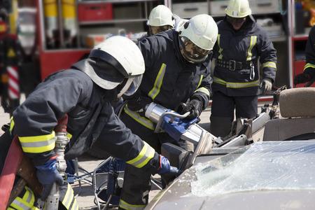 bombera: bomberos con las tijeras neumáticas se abren las puertas del coche después de un accidente de coche