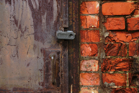 keep gate closed: Fragment of an old metal door closed with a lock and of wall from red brick Stock Photo