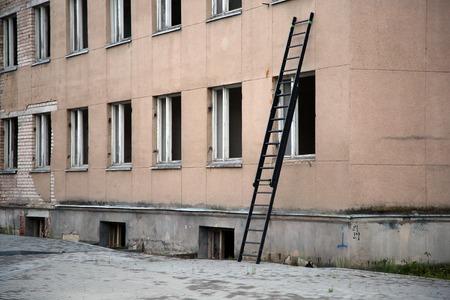 penetracion: Escalera cerca de la construcci�n con la fila de ventanas rotas Foto de archivo