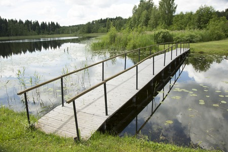 bridge over water: Little wooden bridge over water surface near lake Stock Photo