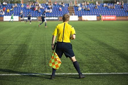 arbitros: Árbitros asistentes con la bandera en el partido de fútbol