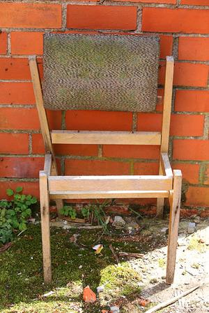 broken chair: Broken wooden chair near the wall from red brick