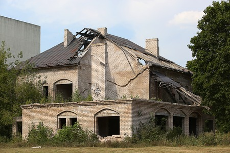 collapsing: collapsing abandoned building - unfinished house with dark windows Stock Photo