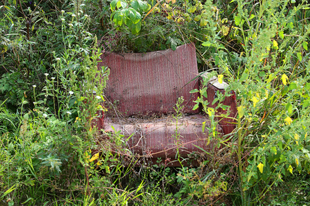 trashed: thrown red chair in the grass Stock Photo
