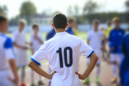 Football player with number 10 in whitw jersey staying back