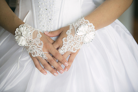cuff bracelet: Hands of bride with decorations in white dress Stock Photo
