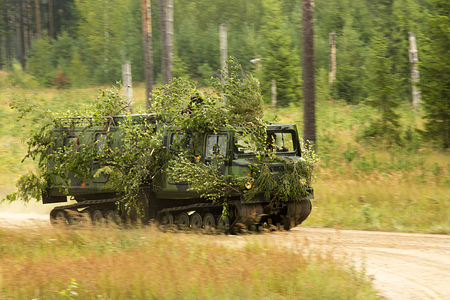 armored car: camouflaged armored car in motion in the forest Stock Photo