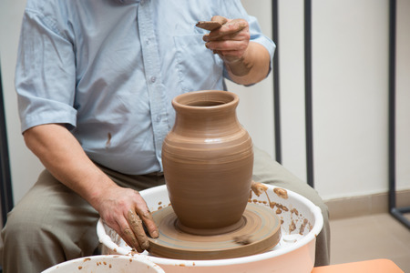 craftswoman: potter working on ceramic jug by hands