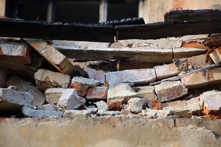 fire bricks: broken cracked wall made of bricks after fire
