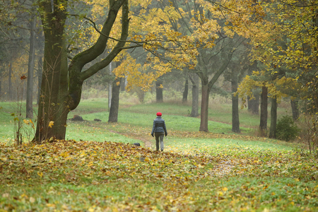 green environment: Park in fall with walking woman in the red beret
