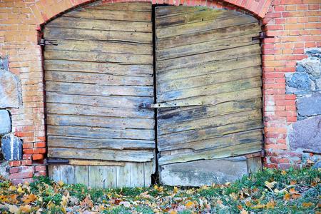 ghost rock: Old cracked door of brick building with lock