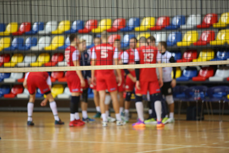Volleyball players in red jerseysat tne background of volleyball net
