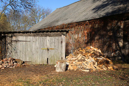 country side: Wooden barn and chopped firewood at country side Stock Photo